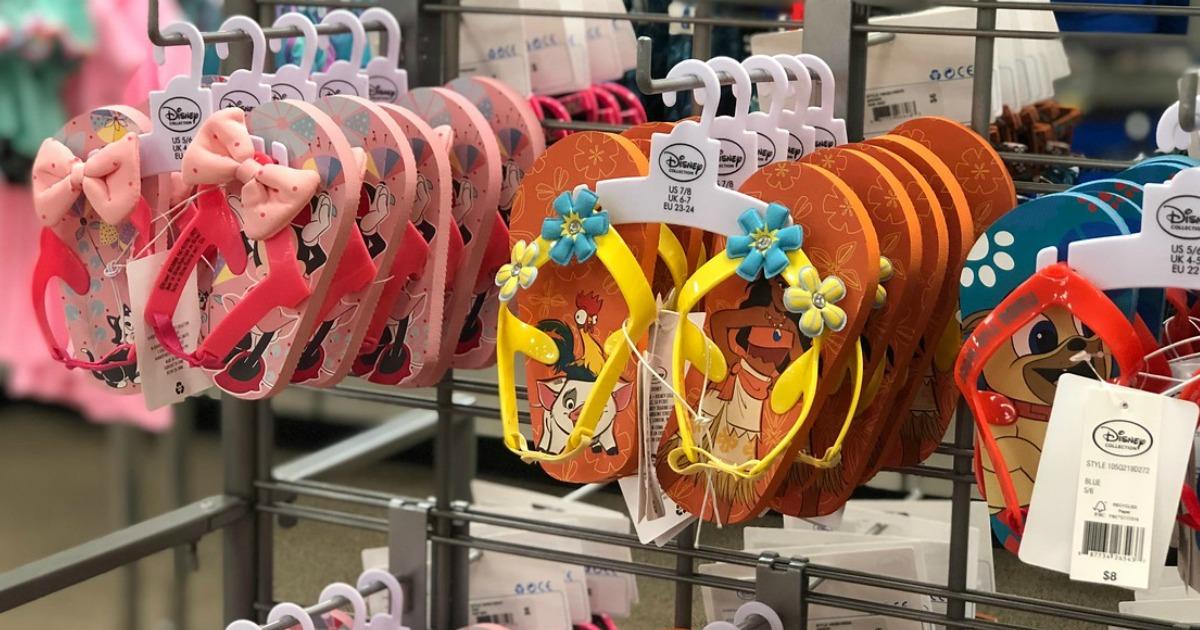 several pairs of kids flip flops hanging on store display