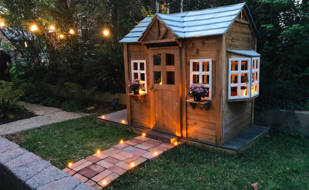 kids wooden playhouse with string lights and pathways - selling your home