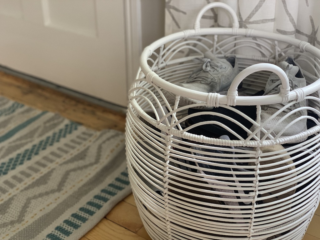 large white basket with shoes by front door