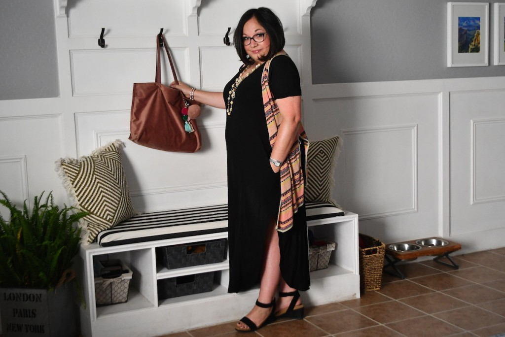 woman standing next to tree hall with black dress and brown leather bag hanging up