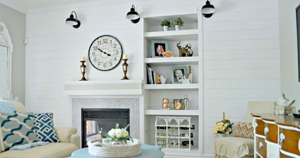 white shiplap wall with fireplace and white mantel with various home decor