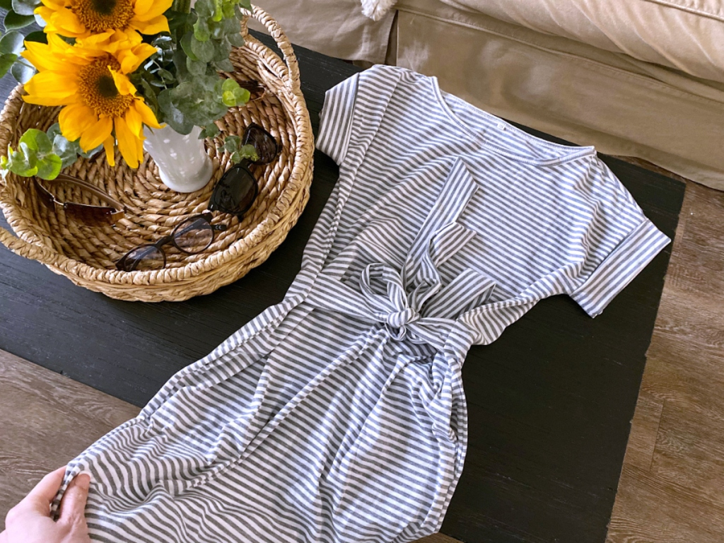 short sleeve stripe dress laying on table with basket full of sunflowers and sunglasses