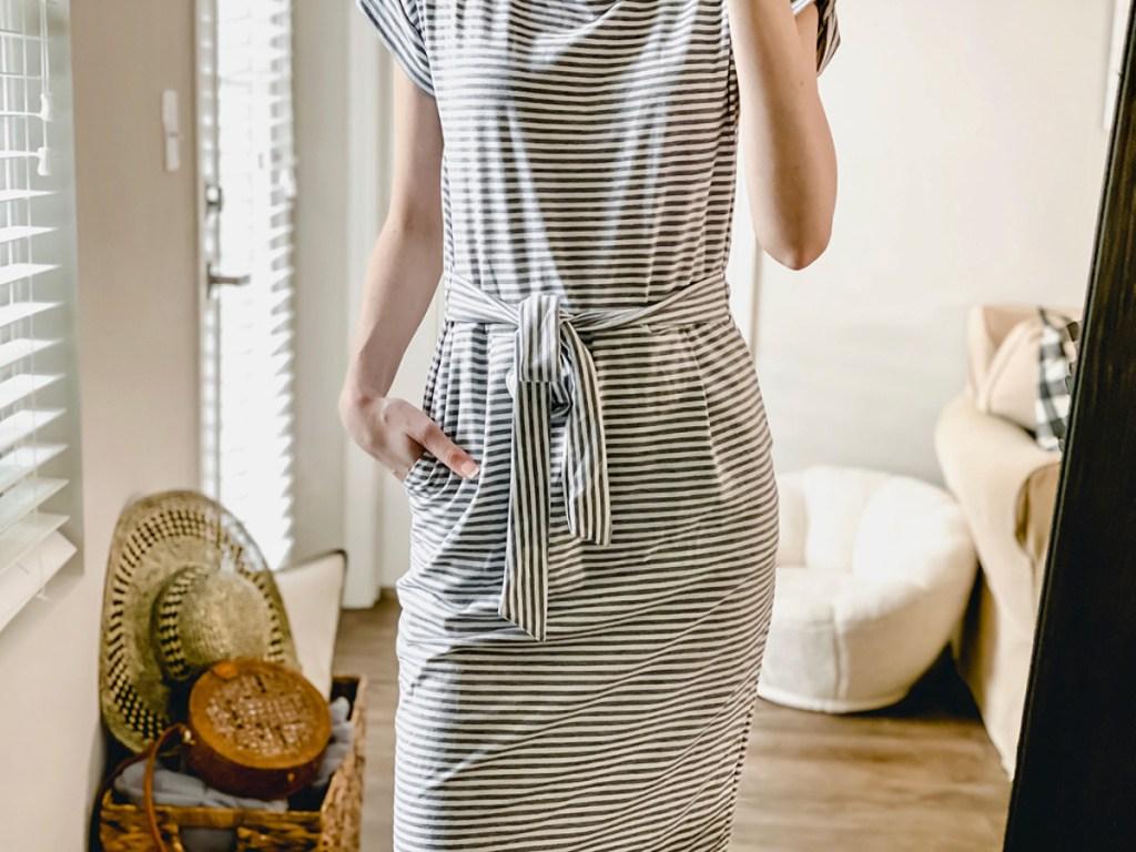 woman wearing black and white stripe pencil dress with tie around waist