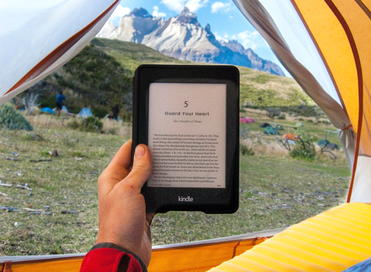 person reading Kindle from tent in mountains