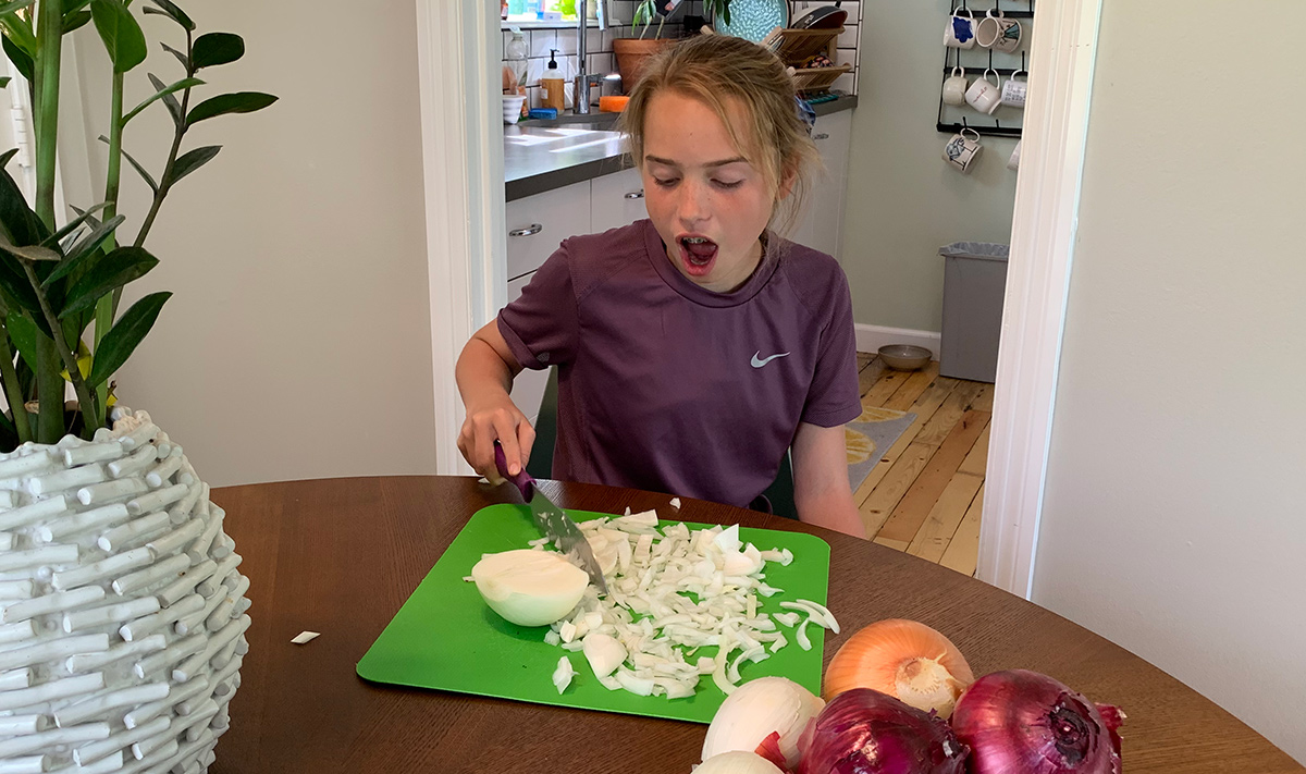 collin's daughter cutting white onion with mouth open to prevent tears