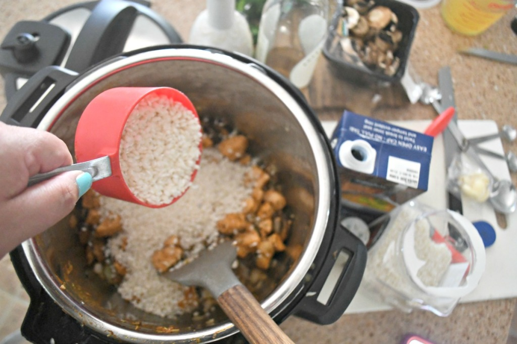 pouring rice in instant pot for chicken risotto dinner