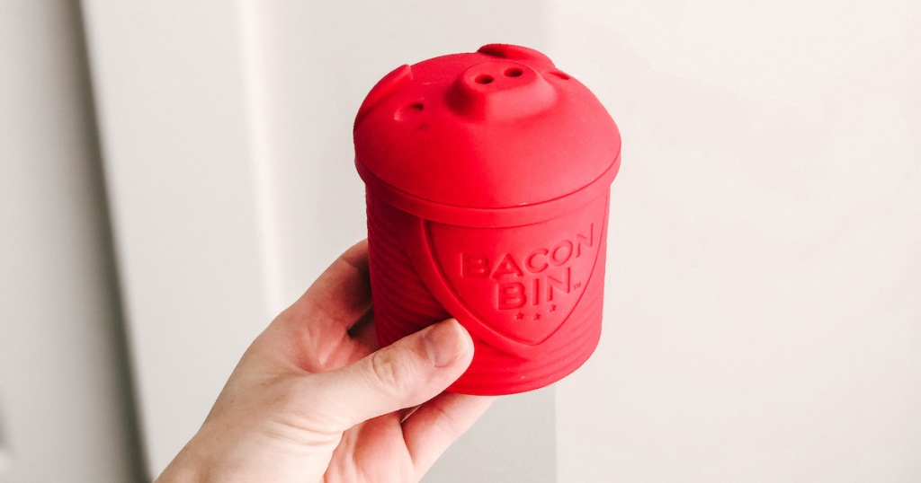 hand holding a red pig shaped bacon bin