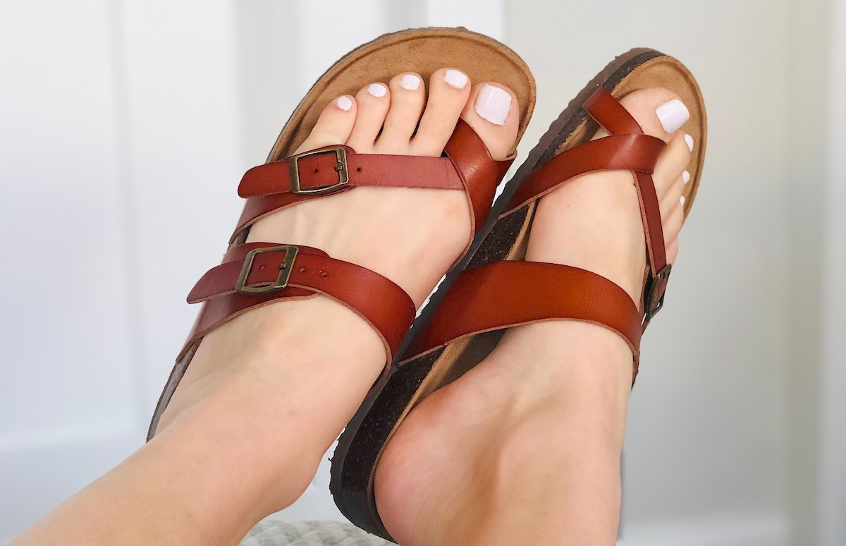 feet wearing strappy brown sandals with buckles
