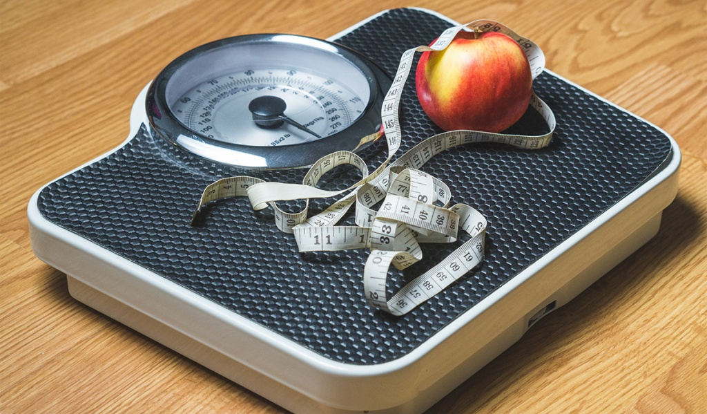 scale with apple and measuring tape on surface
