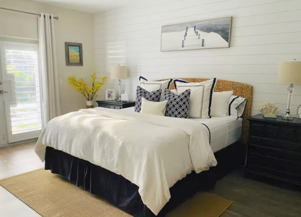 coastal style bedroom with pillows artwork and shiplap wall