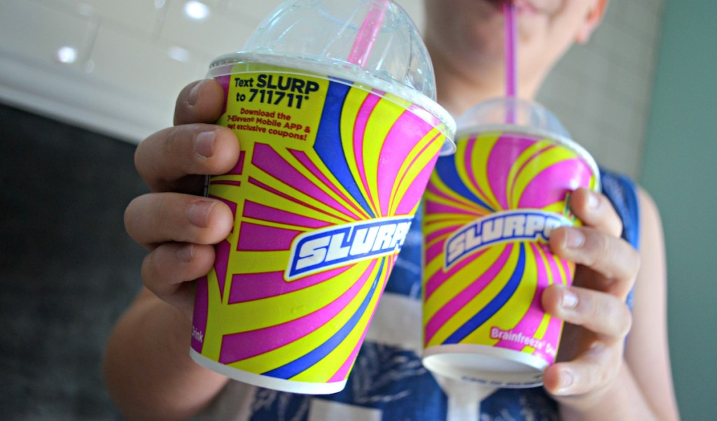 boy holding two cups of slurpees with retro design on outside