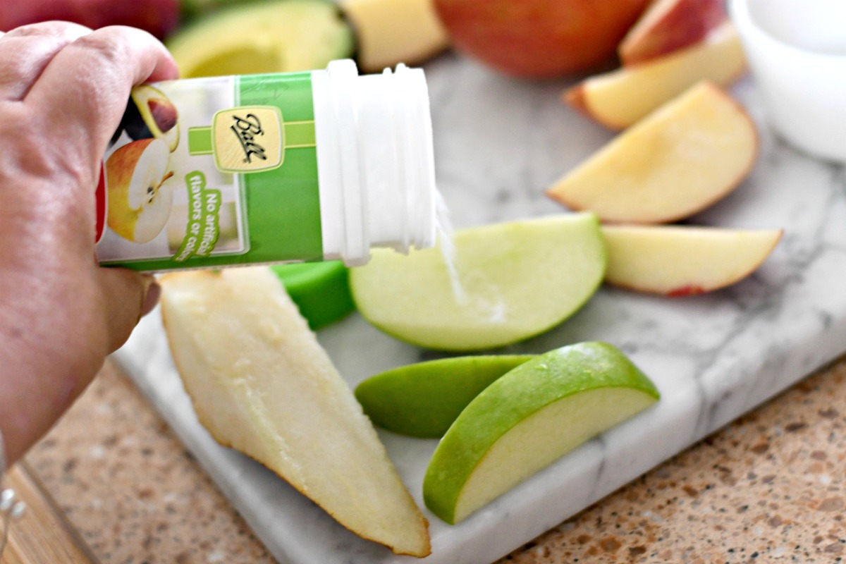 sprinkling ball fruit-fresh onto an apple slice