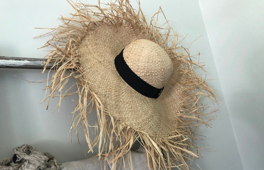 straw seagrass hat with black ribbon hanging on ladder