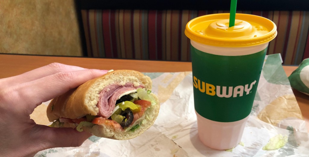 hand holding a small sub with meat and veggies next to tall subway cup