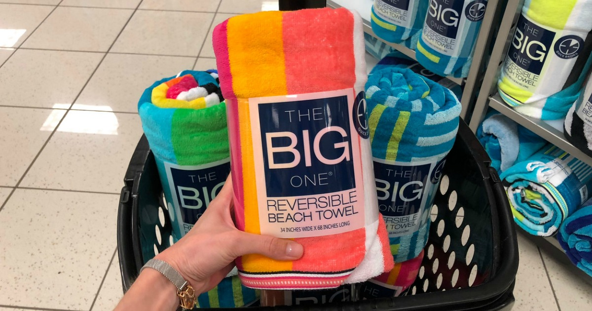 Woman holding The Big One beach towel over basket