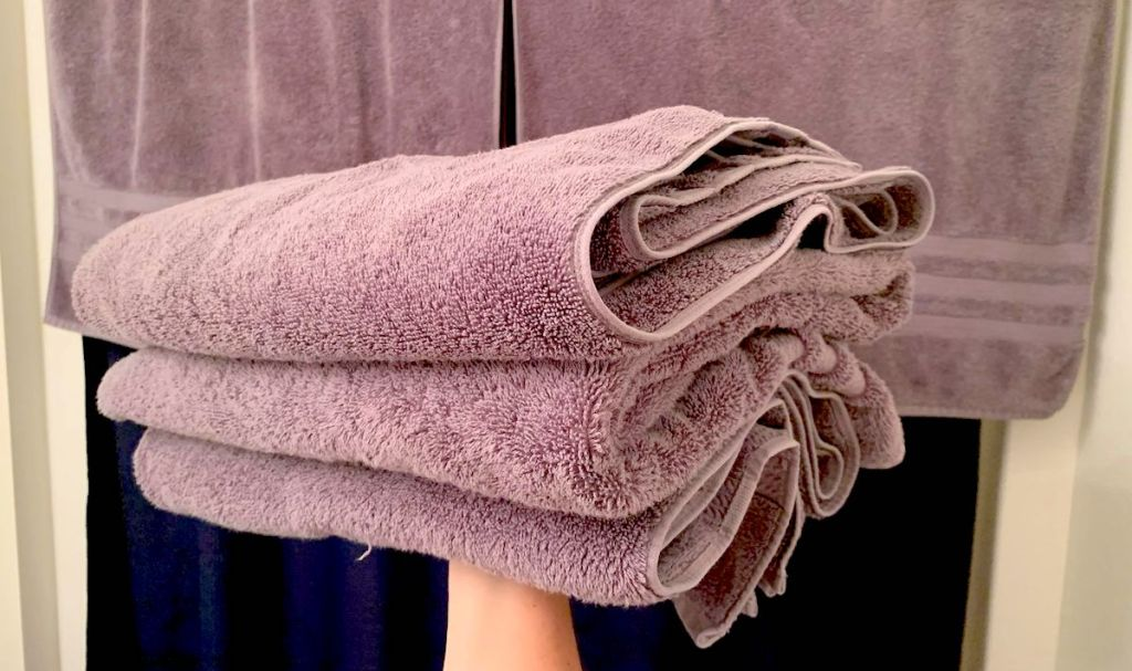arm holding up pile of purple towels