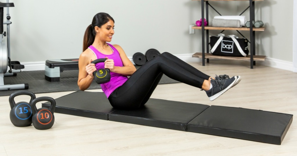 woman wearing a purple tank top and black pants holding weights and doing excercises on a blank floor mat