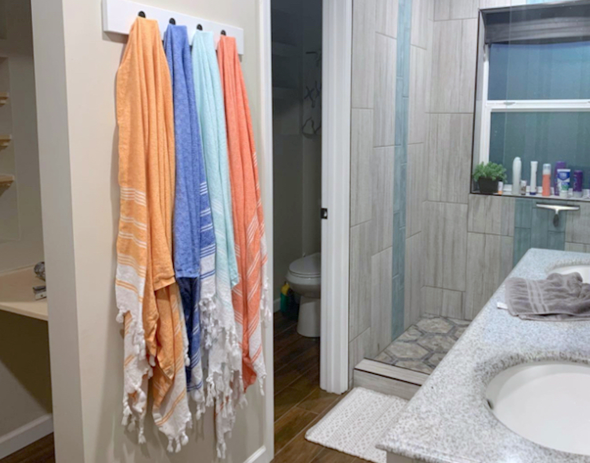 row of bright colorful bath towels hanging on wall in bathroom