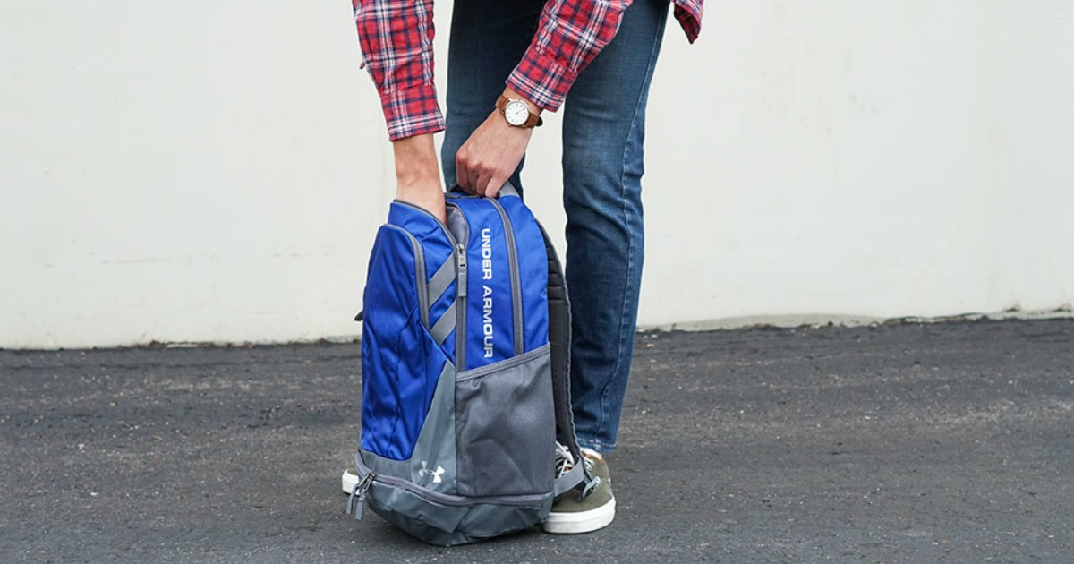 man reaching into an Under Armour Hustle Backpack