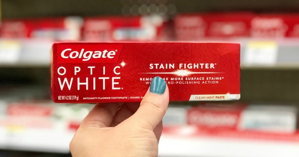 hand holding colgate optic white toothpaste at walgreens