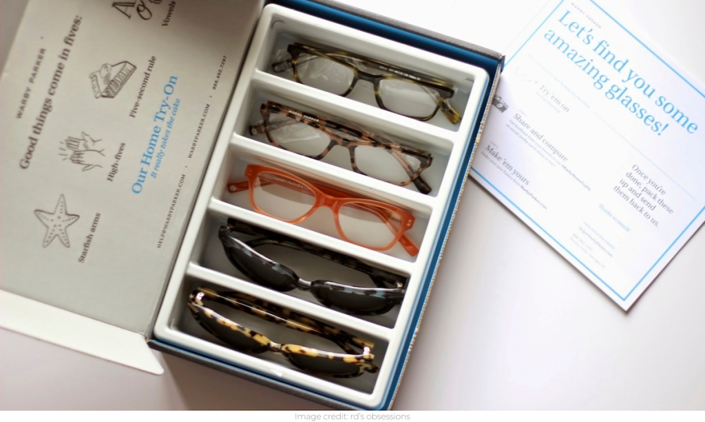 box of five pairs of sunglasses and glasses sitting on white counter