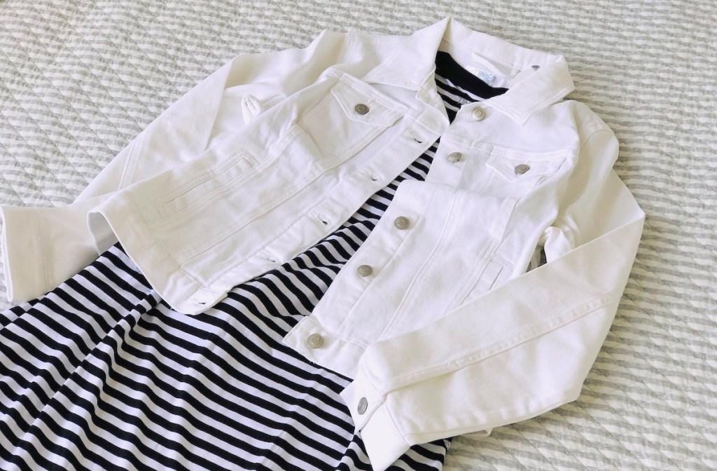 Walmart fashion white jean jacket and black white stripe dress laying on gray blanket