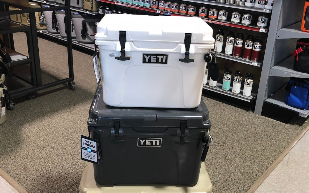 white yeti cooler stacked on top of black yeti cooler with tumblers on shelf in background