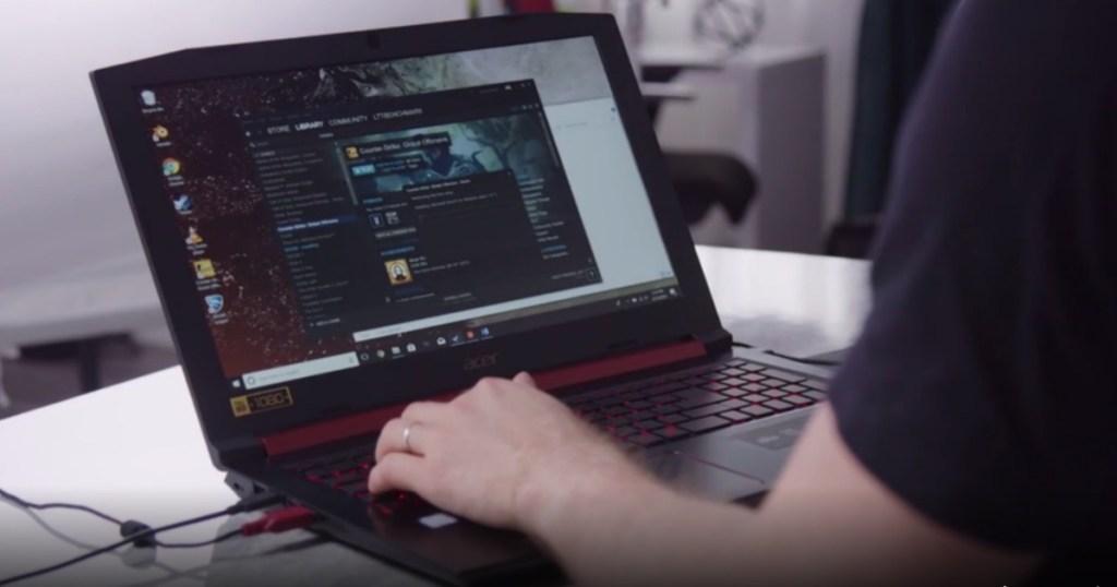 man sitting at desk typing on laptop