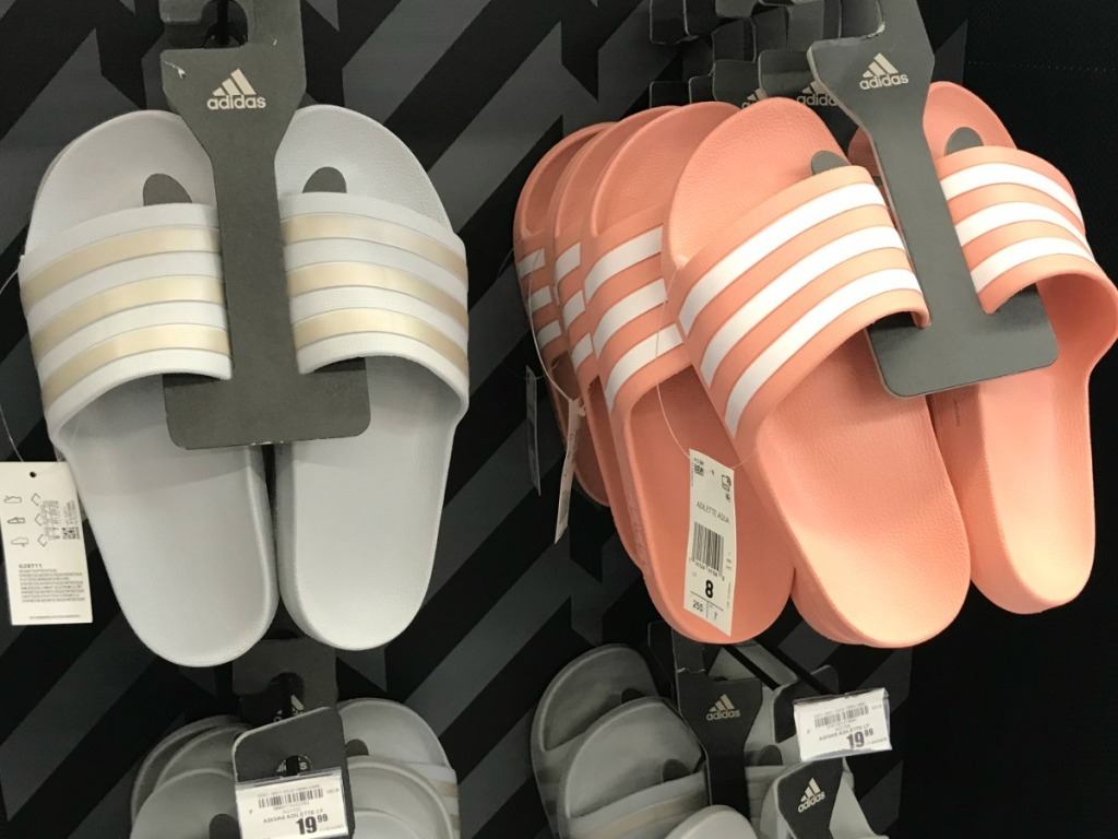 Pink and white Adidas slides hanging on tack at Academy