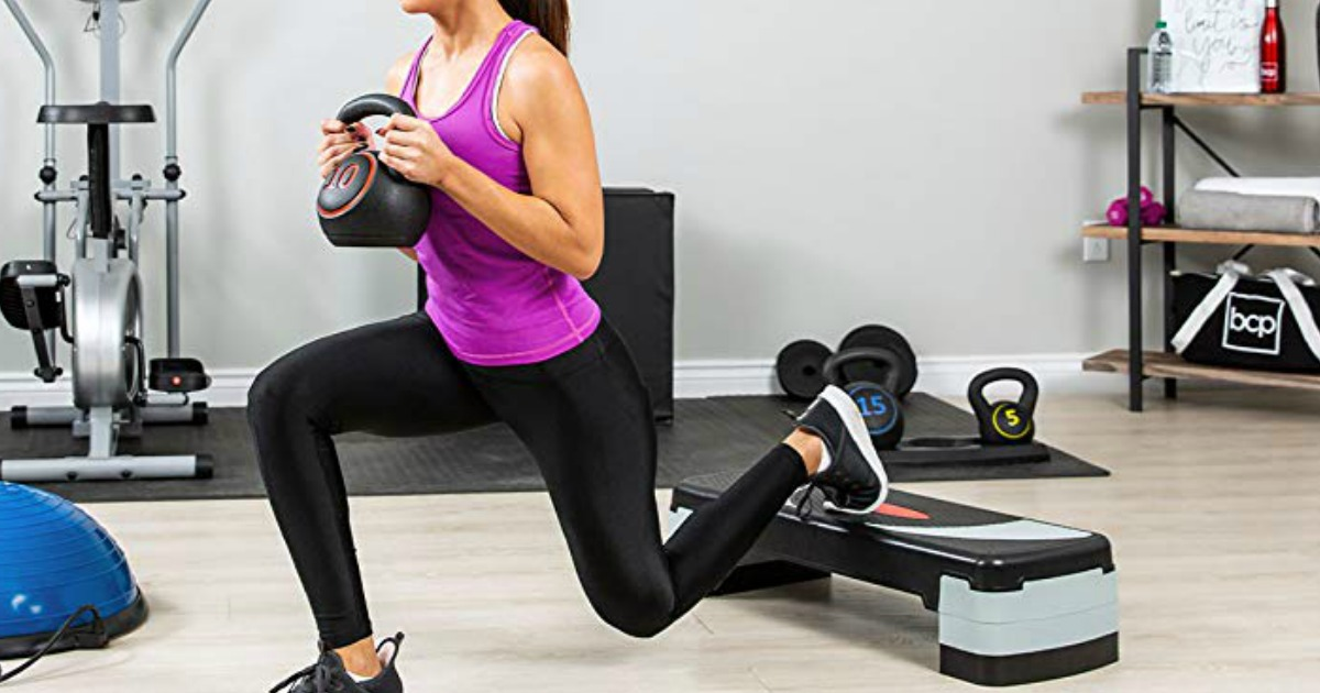 woman in gym using step platform to do exercise