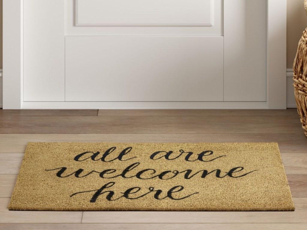 All Are Welcome Here Tufted Door Mat next to a front door