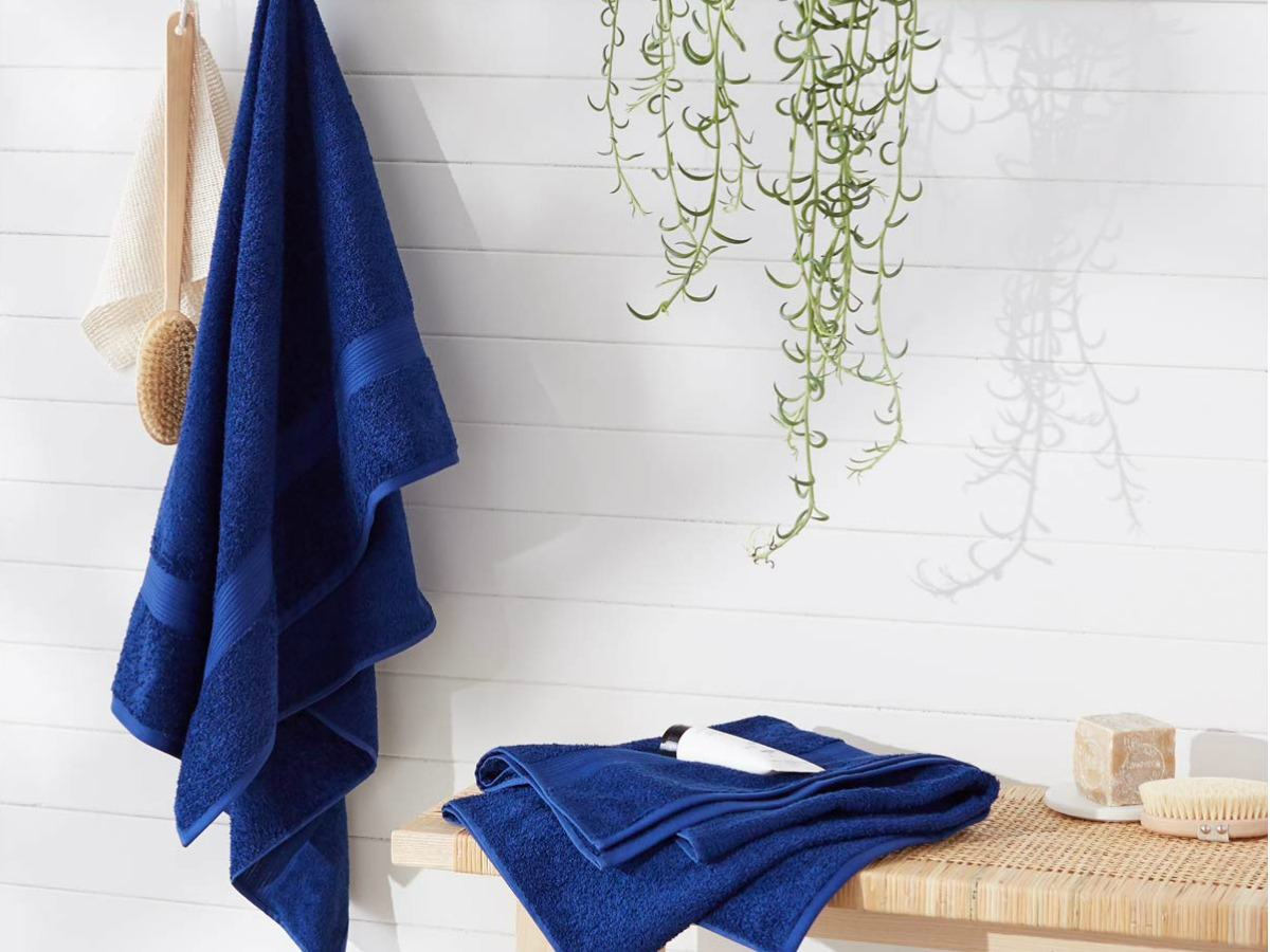 navy towel hanging on hook with folded navy towels on wicker table