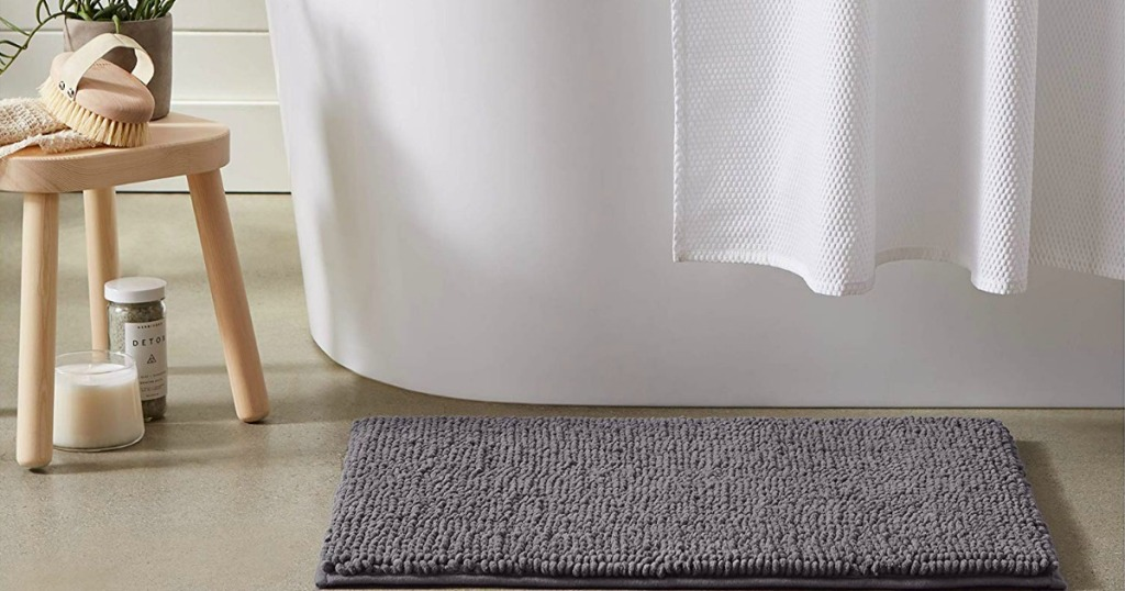 gray chenille mat in front of tub in bathroom