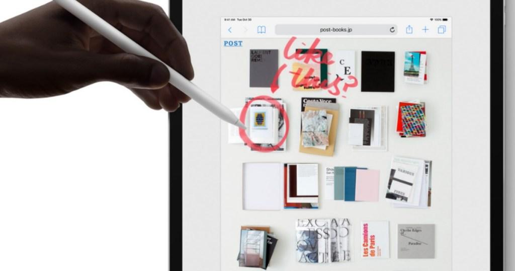 hand holding Apple Pencil near tablet