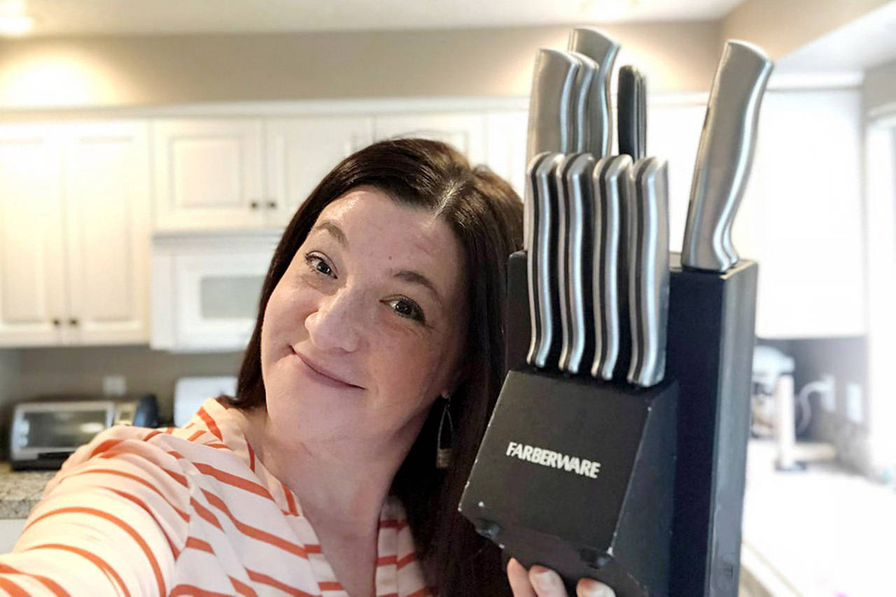woman holding up knife set from sears