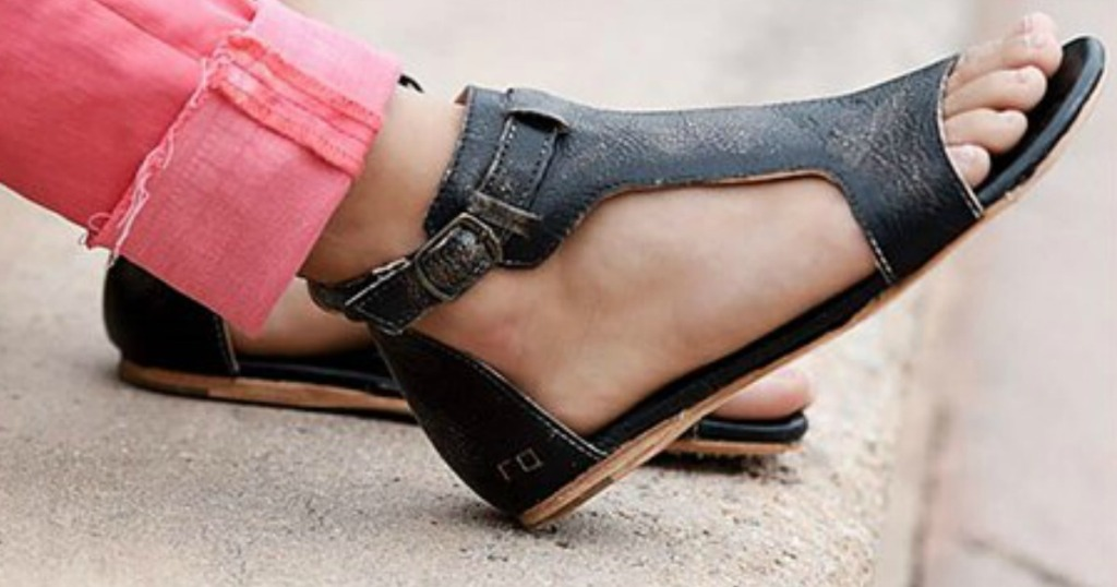 leg wearing pink jeans and black sandals
