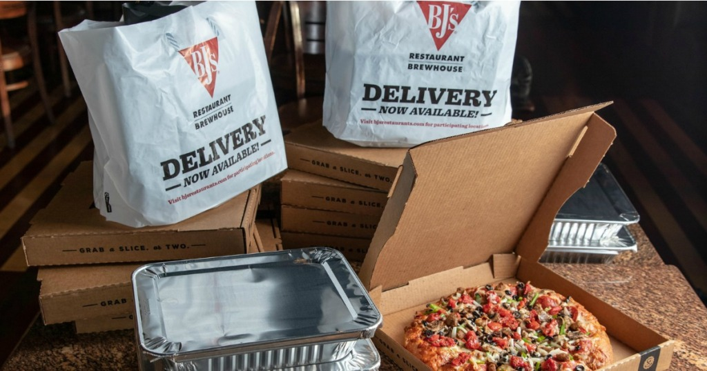 Bj's restaurant to-go bags next to catering pans and a pizza box with fresh pizza