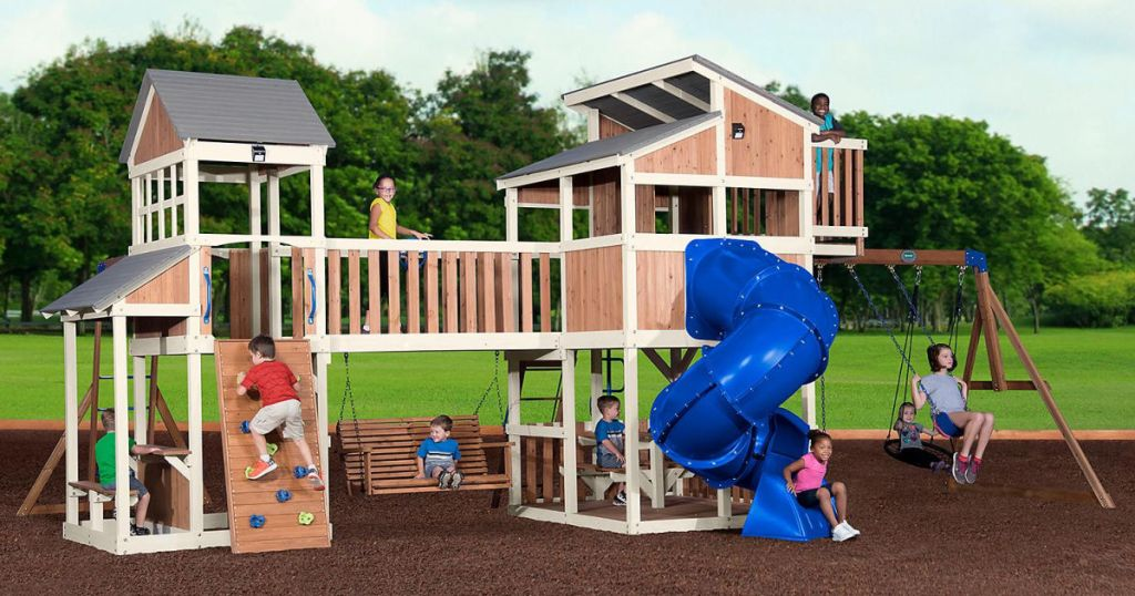 many children playing on large play set in backyard
