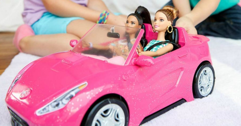 pink Barbie convertible car with two Barbie dolls in it