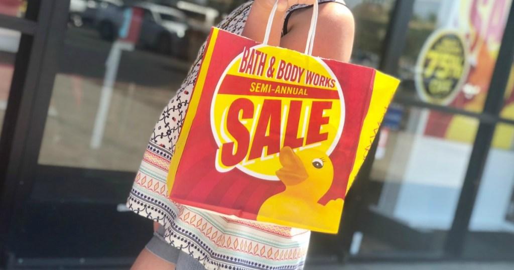 girl carrying bath $ body works semiannual sale bag