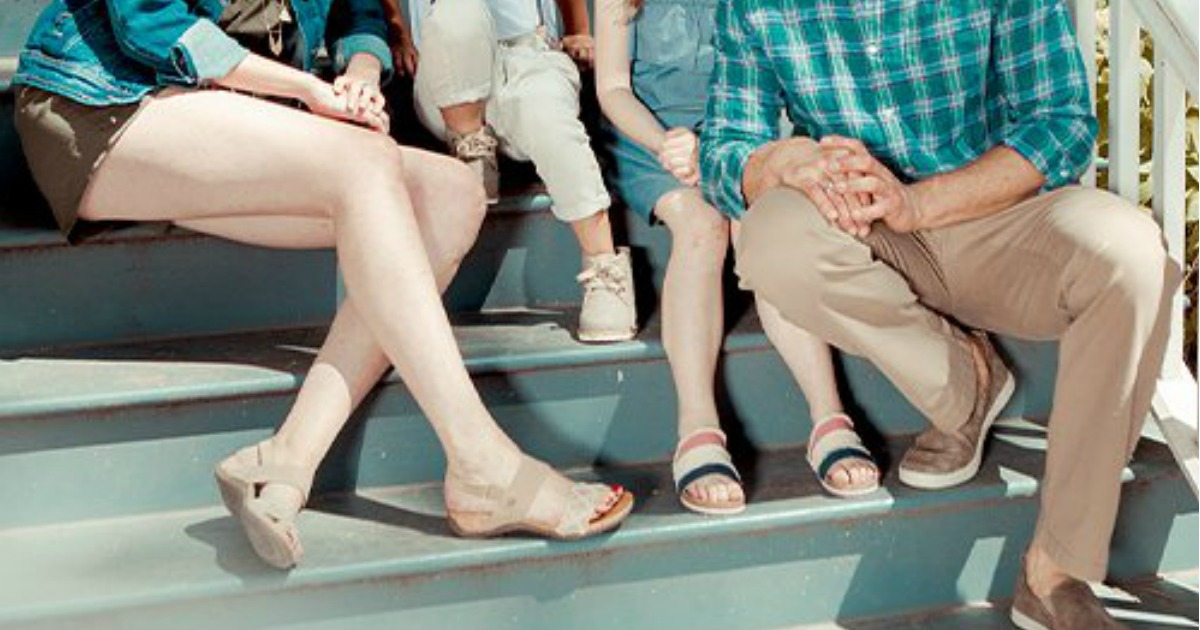 Family sitting on stoop steps all wearing Bearpaw sandals
