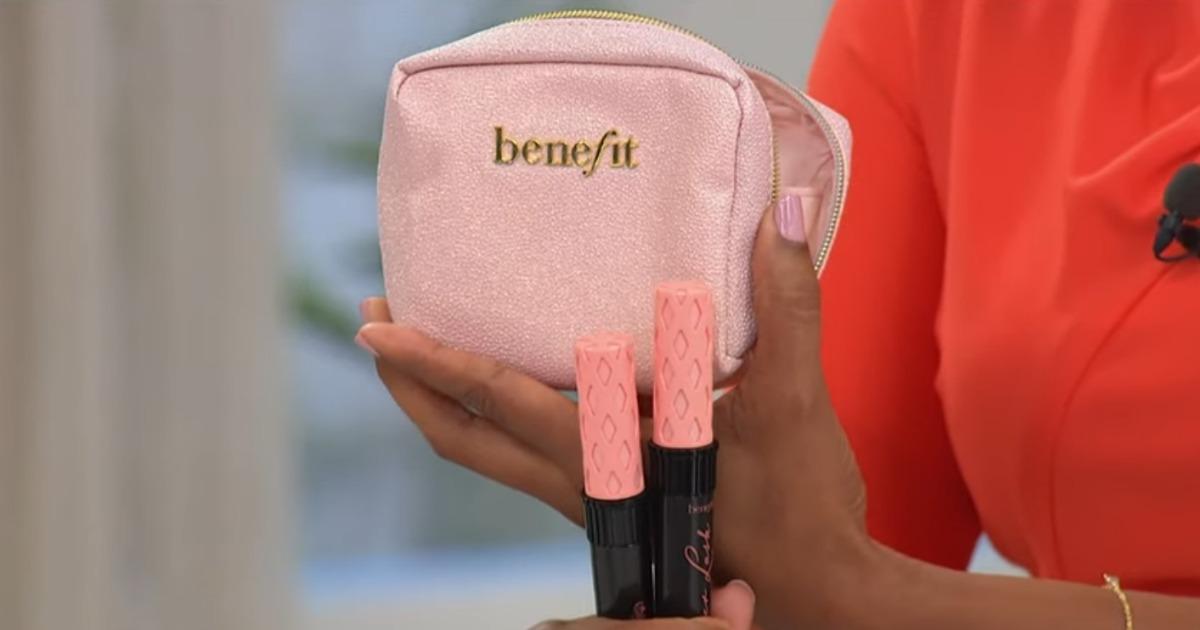 Woman holding 2 Benefit Cosmetics Roller Lash Mascaras and pink Benefit makeup bag