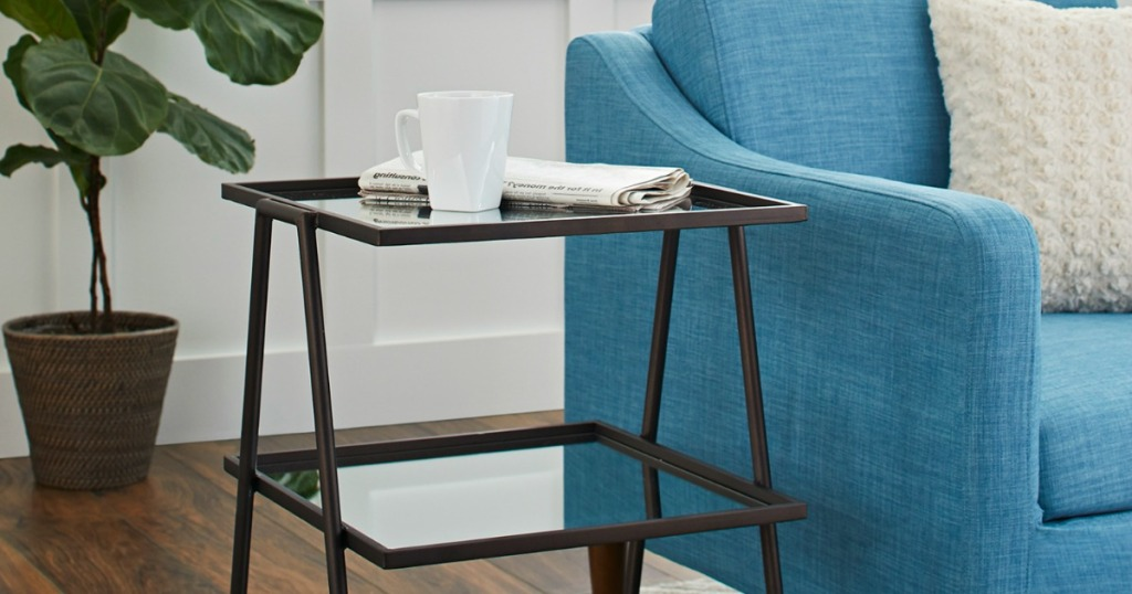 Better Homes & Gardens Metal & Mirrored 3 Shelf Accent Table next to blue couch