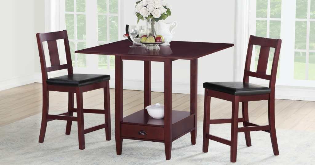 Mahogany colored counter height dining set with vase of roses on top