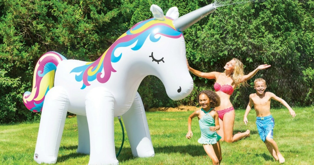Mom and two kids playing with a HUGE unicorn inflatable yard sprinkler