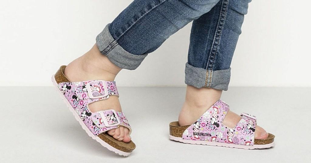 Girl wearing Birkenstock Kids Arizona Sandals in Disney Minnie Mouse print