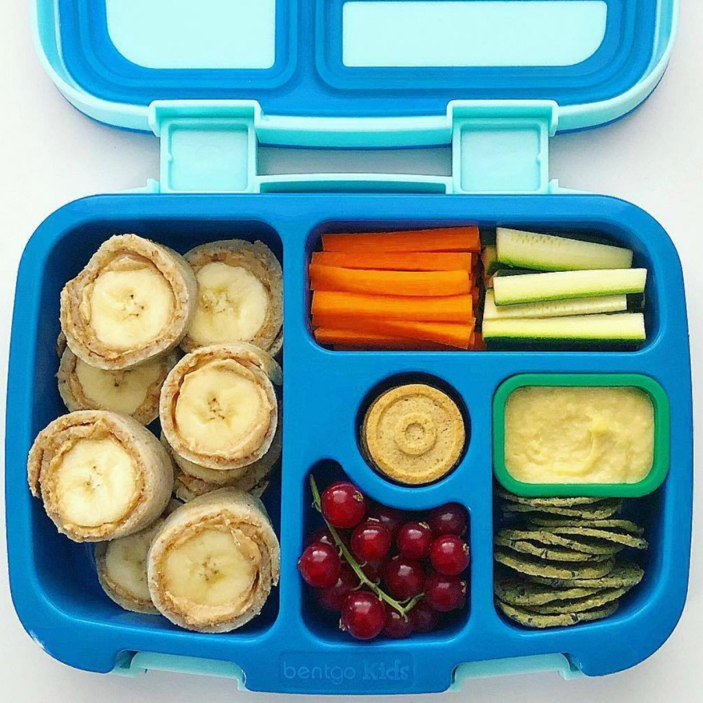 Blue bento kids lunch with veggies, fruit, hummus, and banana roll-ups