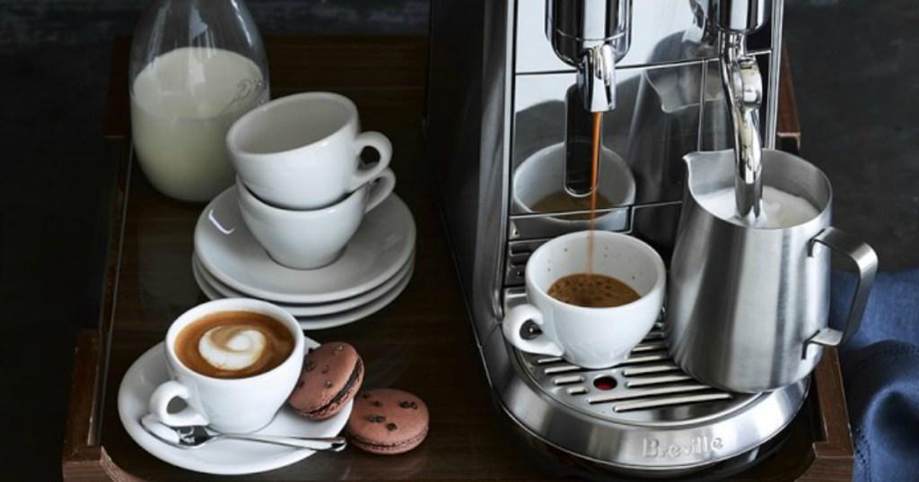 Breville Espresso Machine making espresso with cups and plates