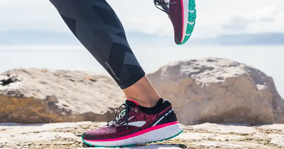 black Brooks Ghost 11 running shoes with pink and teal accents on lady running on trail