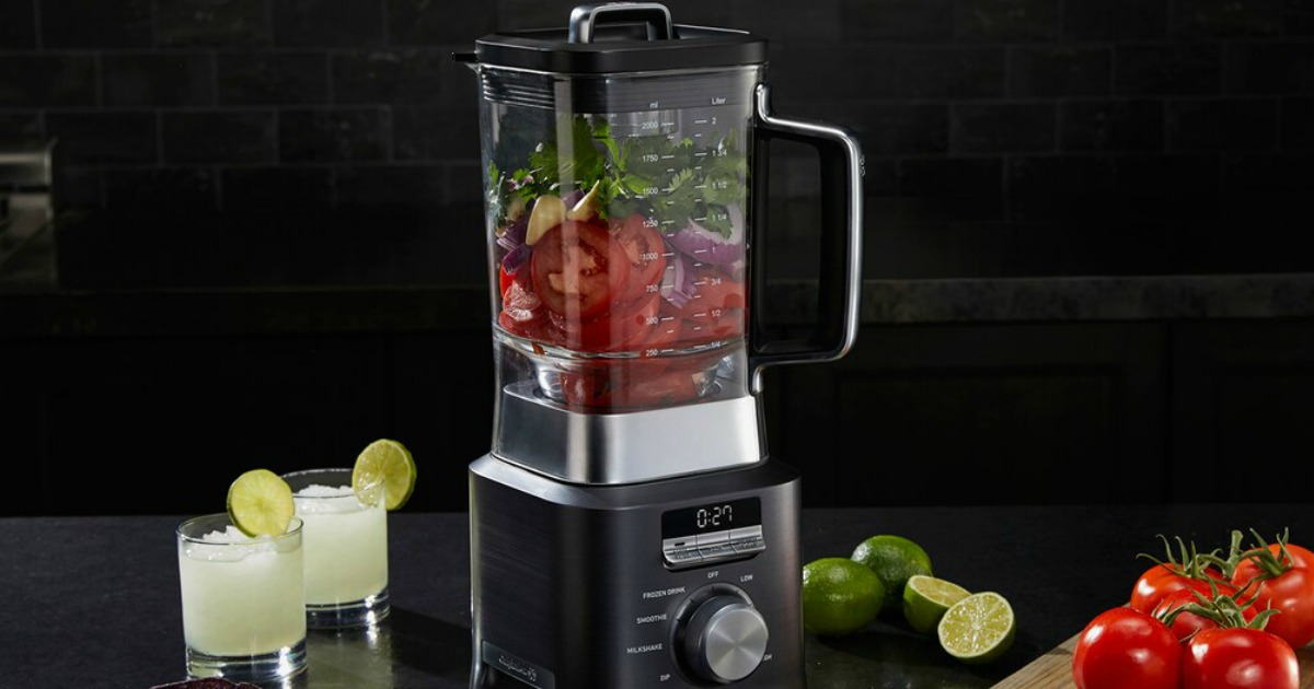 blender bleding veggies with drinks and limes beside it